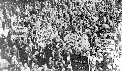 """Maj 1920 r. Demonstracja robotnicza w Płocku. Widać hasła KPRP,  m.in. """"Precz z wojną zaborczą"""" (chodzi o atak Piłsudskiego na rewolucyjną Rosję)."""