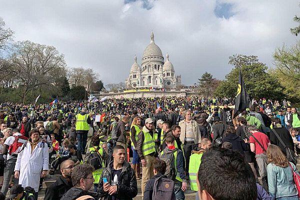 """23.03.19 Akt XIX – czyli dziewiętnasta sobota protestów. """"Żółte kamizelki"""" podały, że wzięło w nich udział 127 000 osób. Macron przekroczył kolejną granicę – wyprowadził na ulice wojsko. To żołnierze uczestniczący od 2015 roku w antyterrorystycznej """"Opération Sentinelle"""". Wojskowy gubernator Paryża generał Bruno Le Ray powiedział, że wojsko będzie mogło """"otworzyć ogień"""" do demonstrujących. Jednak protestujący nie odpuszczają. Nawet według danych rządowych więcej osób wyszło na ulice w sobotę niż w zeszłym tygodniu.  Na zdjęciu: protestujący pod symbolicznie ważnym kościołem Sacré-Cœur, na wzgórzu Montmartre, w Paryżu. Kościół ten zbudowano, by pokazać potęgę władzy po tym, jak Komuna Paryska została w 1871 r. utopiona w krwi."""