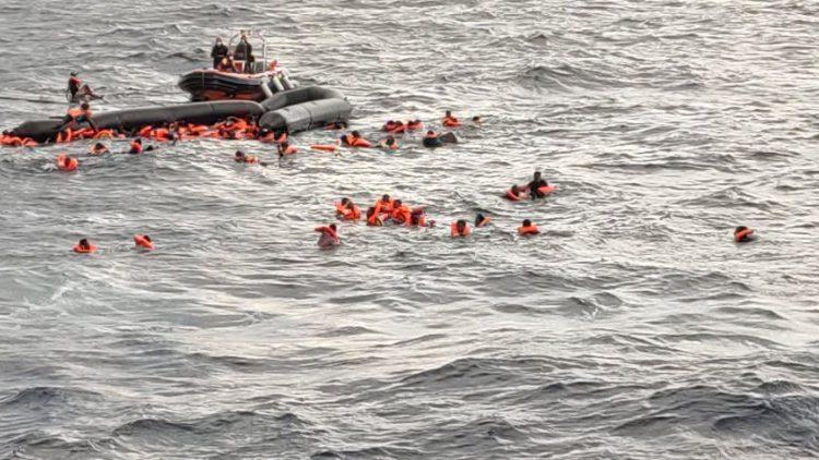 Uchodźcy w wodzie czekający na ratunek.