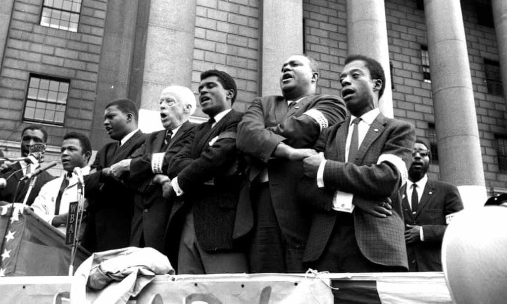 1963 r. James Baldwin z aktywistami ruchu praw obywatelskich na pierwszym planie, pierwszy z prawej.